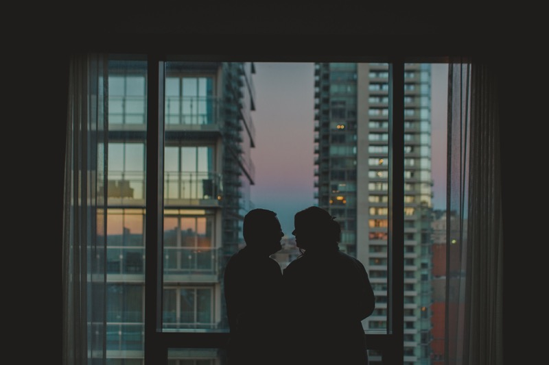 The two of us in silhouette, standing in front of a hotel window looking out at the city
